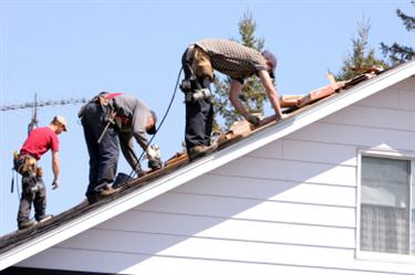 Roof Installation in Agoura Hills CA. Three roofers laying new shingle on a roof in Agoura Hills.